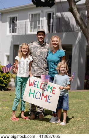 Happy caucasian soldier father embracing wife and children with welcome sign and flags outside home. soldier returning home to family.