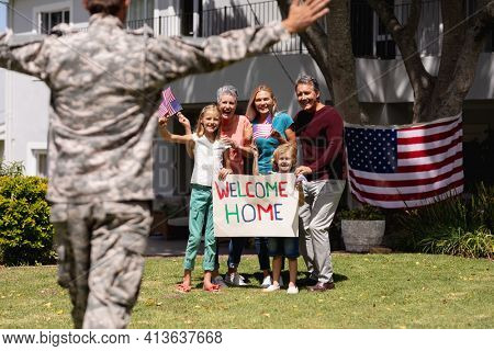 Caucasian soldier father and family meeting outside home with welcome sign and american flags. soldier returning home to family.