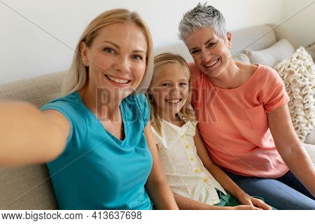 Caucasian mother sitting on couch taking selfie with smiling daughter and grandmother. happy three generation family spending time together at home. other