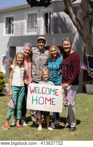 Happy caucasian soldier father, wife, children and parents outside home with welcome sign and flags. soldier returning home to family.