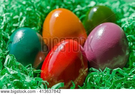 Easter Nest With Multicolored Paschal Eggs. Easter Eggs Arranged In A Nest, Made Of Green Shredded P