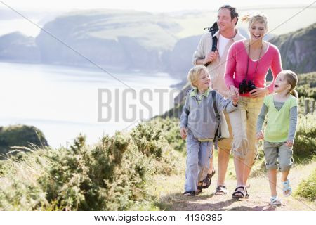 Families Walking On Cliffside Path Holding Hands And Smiling