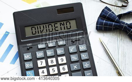 A Calculator Labeled Dividend Lies On Financial Documents In The Office. Business Concept.