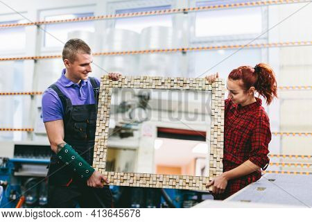 Man and woman showing a mirror with handmade wooden frame in glazier workshop. Small business