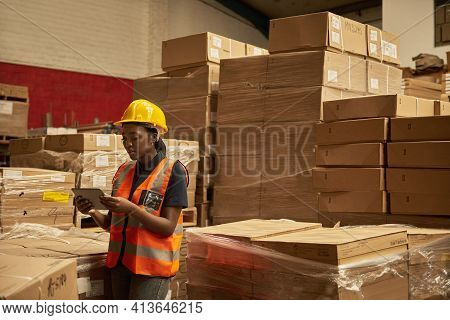 Young African Female Warehouse Worker Doing Inventory Using A Tablet
