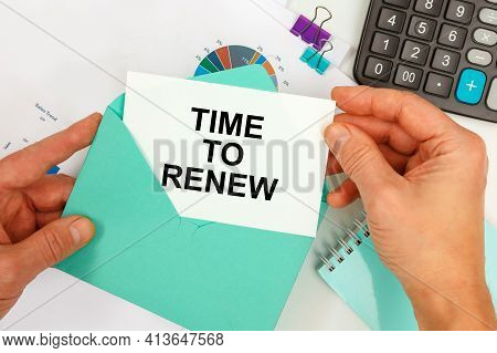 The Businessman Takes Out A Card From The Envelope With The Text Time To Renew, On The Background Of