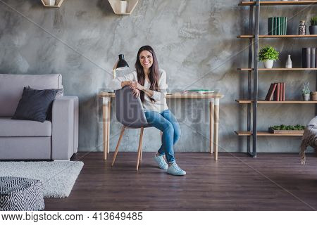 Photo Of Business Lady Sit Chair Look Camera Wear Eyewear White Sweater Jeans Footwear In Living Roo