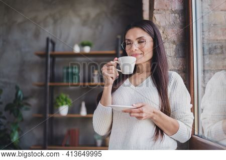 Photo Of Cheerful Lady Smell Coffee Aroma Close Eyes Enjoy Wear Eyeglasses White Pullover In Living