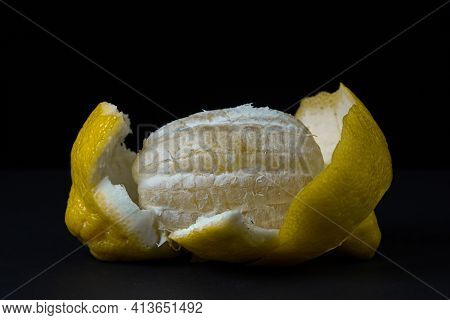 Lemon On A Dark Background. A Peeled Lemon Lies In A Peel On A Black Background. Creative Photo Of L