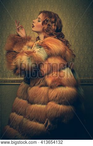 Beautiful fashionable model with curly red hair posing in a luxurious fox fur coat on a vintage background. Winter beauty fashion. Fur coat style.