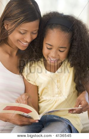 Woman And Young Girl Sitting In Living Room Reading Book And Smiling