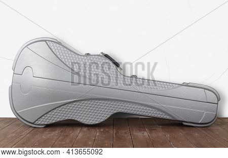 Music And Sound - Front View Silvery Acoustic Guitar Hard Case On A White Wall And Wooden Background