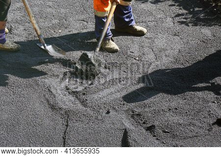 Road Street Repairing Works. Workers Level The Asphalt With Shovels. Construction Workers During Asp