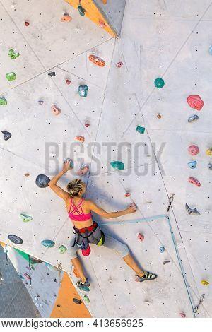 A Woman Climbs A Climbing Wall, A Climber Is Training On Artificial Terrain, Rock Climbing In The Ci