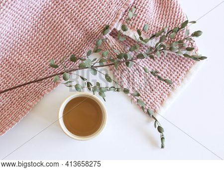 Closeup Of Green Eucalyptus Leaves Branches, A Cup Of Coffee, And Pink Plaid On White Table Backgrou