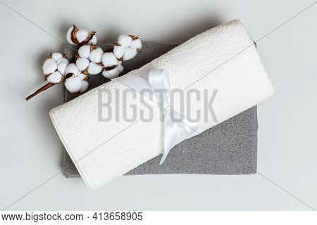Close-up Top View Of A Stack Of Rolled Up White And Gray Towels With A Cotton Branch.