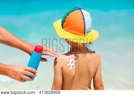 Mom Applying Sunscreen On Child. Safe Beach Fun.