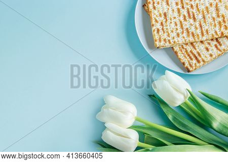 Happy Passover Concept. Matzo And White Tulips On Blue Background. Religious Jewish Holiday Pesach.