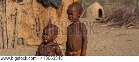 Khorixas. Namibia, January 13. 2020: Side View Of Two Himba Tribe Boys Stay At The Himba Village, Ne
