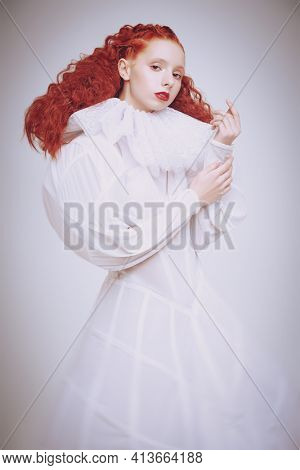 Art portrait of a refined fashion model girl with lush red curly hair posing in a white haute couture dress. Studio shot on light grey background.