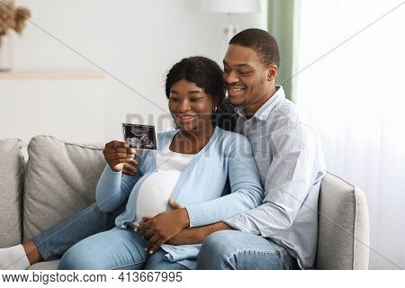 Smiling Pregnant Black Couple Holding Ultrasound Image, Home Interior