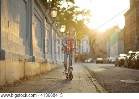 Adorable Young Girl Riding Her Scooter In A City Park On Sunny Autumn Evening. Pretty Preteen Child