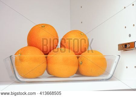 Organic Oranges In A Glass Container That Is In A Kitchen Cupboard. Close Up.