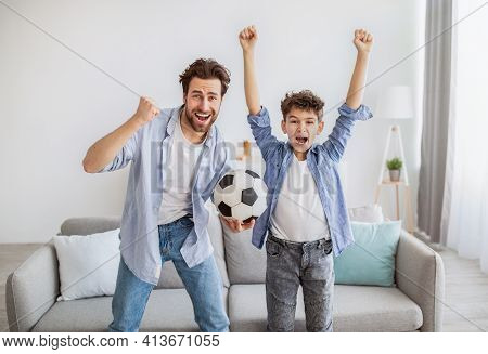 Emotional Soccer Fans. Cheerful Dad And Son Cheering With Football Ball, Watching Match On Tv