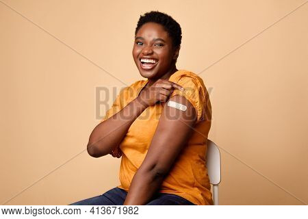 African Woman Showing Covid-19 Vaccinated Arm With Plaster, Beige Background