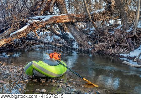 inflatable whitewater kayak at river log jam - Poudre River in Fort Collins, Colorado, winter or early spring scenery