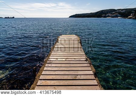 A Wood And Concrete Pier Leading Out Into The Clear Refreshing Waters Of The Mediterranean Sea In A