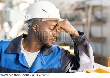 Young tired factory worker of African ethnicity in workwear and hardhat touching his forehead while resting in front of camera in workshop