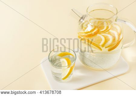 Lemon Detox Water In The Morning On Yellow Table. Healthy Antioxidant Drinking Water.