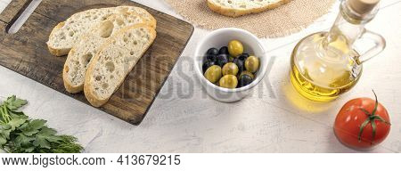 Banner With Sliced Bread On Serving Board Served With Olives, Tomatoes, Olive Oil And Fresh Herbs On