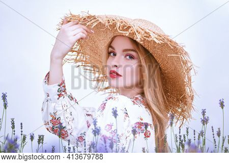Gentle blonde girl in a straw hat and a summer blouse poses on a white background with lavender flowers. Light fresh makeup in pink colors. Spring and summer fashion.