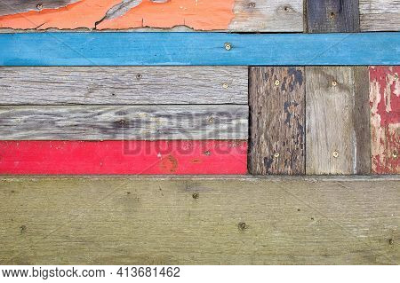 Faded Orange, Red And Blue Paint On Gray Weathered Wood