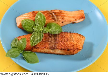 Fried Red Salmon With Basil Leaves. Close Up.