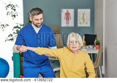 Senior Patient While Exercise Treatment With His Physiotherapist. Rehab At A Medical Center