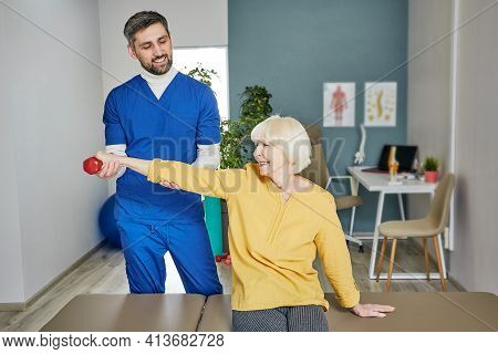 Senior Woman Lifts A Dumbbell, Doing Treatment Exercise With Her Physiotherapist. Physio Treatment A