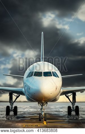 Modern White Airplane Against A Dramatic Sky