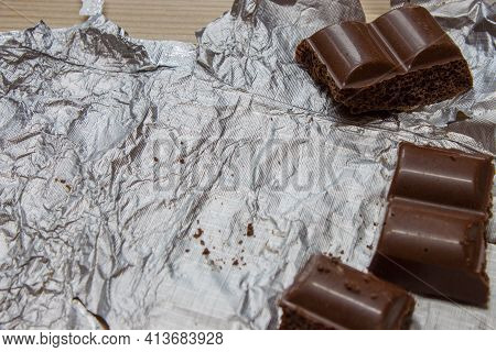 Chocolate Ba On Black Wooden Background Top View. Chocolate Wrapped In Aluminum Foil On A Wooden Boa