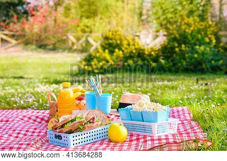Lunch In The Park On The Green Grass. Summer Sunny Day And Picnic Basket. Popcorn And Sandwiches For