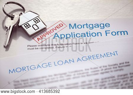 Mortgage application form and loan agreement with  key on house shaped keyring