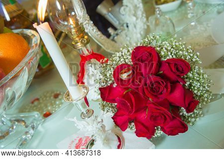 Red Ribbon . Red Engagement Flowers On White Table . Bride And Groom With Engagement Gold Rings Put