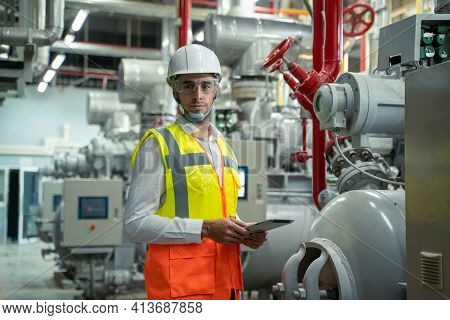 Mechanical Maintenance Technician Inspecting Pressure Gauge Of Heating System In Heating Plant.