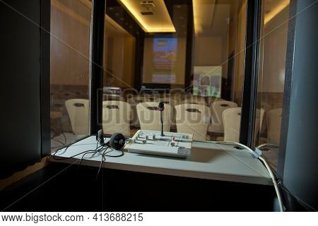 Soft Focus Of Wireless Conference Microphones And Notebook In A Meeting Room. Translators Cubicle .