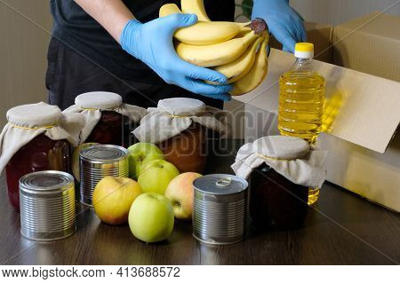 Volunteer In Protective Gloves Pack Products In The Box. Social Assistance, Food Delivery During The