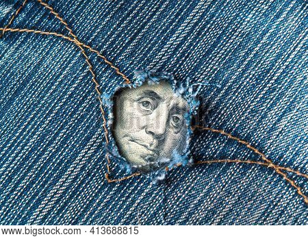 A Hole In The Pocket Of Denim Pants From Which Dollars Are Visible. Symbolizes Crisis Or A Hole In T