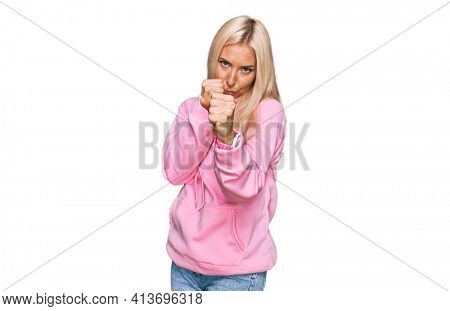 Young blonde woman wearing casual sweatshirt ready to fight with fist defense gesture, angry and upset face, afraid of problem