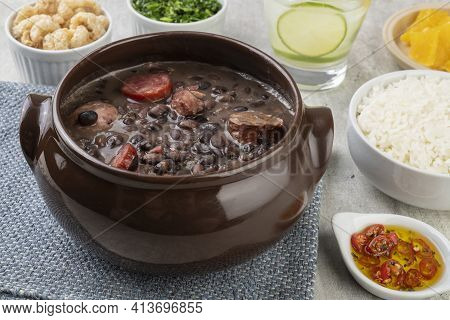 Traditional Brazilian Feijoada With Rice, Orange, Kale, Cracklings, Pepper And Caipirinha.